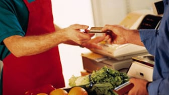 Close-up of cashier taking credit card from customer at grocery store