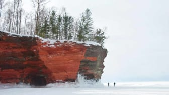 Red sandstone cliffs at the Apostle Islands National Lakeshore, Lake Superior, in winter. Lake is frozen and two small figures walking on the ice emphasize the height of the cliffs.