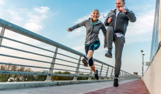 A retired couple skips along a walkway