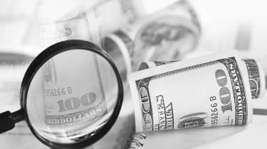 Image of selective focus shot of magnifying glass and hundred dollars bills