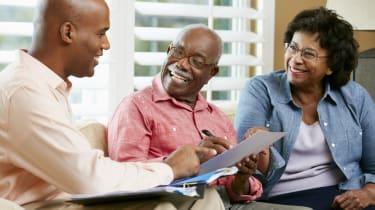 Financial Advisor Talking To Senior Couple At Home Smiling