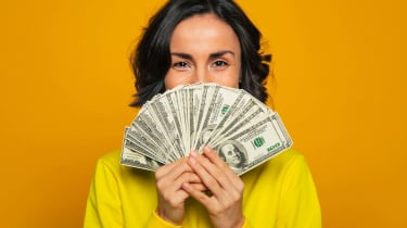 A woman holds a bunch of money like a fan in front of the bottom half of her face.
