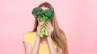 A woman holds a bunch of broccoli in front of her face.