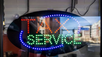 """picture of neon sign in window saying """"tax service"""""""