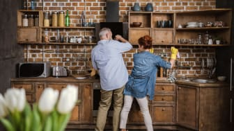 Back view of mature couple having fun while washing dishes in kitchen