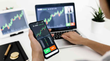An investor using a phone and other digital devices to view their stock performance