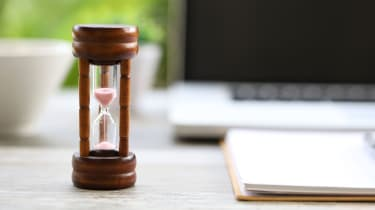 Picture of hourglass running out with computer in background