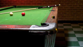 A pool table in a basement.