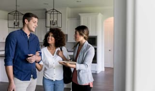 Young couple smile as they talk with a female real estate agent. The real estate agent is showing them a new home.
