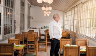 A restaurant owner stands among empty tables.