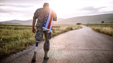 picture of an amputee soldier walking on a road with an American flag over his shoulder
