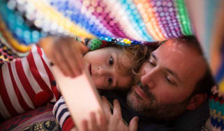 A dad and his little girl look at his phone under a blanket.