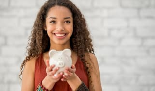 A teenage girl holds a piggy bank and smiles.