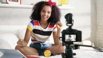 Happy girl at home speaking in front of camera for vlog. Young black woman working as blogger, recording video tutorial for Instagram, Facebook and Internet