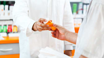Close-up shot of pharmacist's hand giving a bottle of pills to a mature adult custoer in the drugstore.