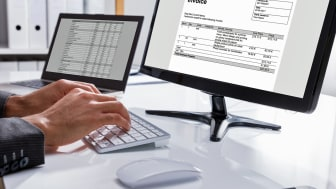 Close-up Of A Businessperson's Hand Checking Invoice On Computer At Workplace