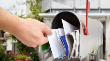 Close-up Of Man's Hand Taking Letter From Mailbox Outside House