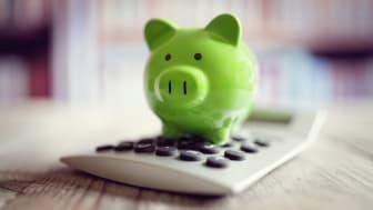 A piggy bank sitting on a calculator