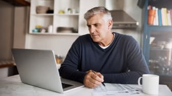 Shot of a mature man going through paperwork while working on a laptop at home