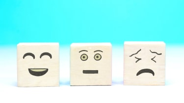 Three blocks with drawn on faces: One smiling, one neutral and one sad.