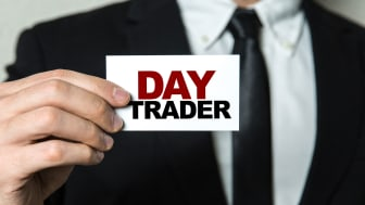 "picture of man in suit holding note saying ""Day Trader"""