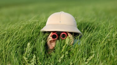 A person in a safari hat looking through binoculars