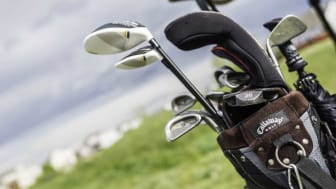 Peyton, Colorado, USA - June 13, 2015: A horizontal format shot of a Callaway golf bag filled with assorted golf clubs on the back of a golf cart. In the golf bag are Ping Eye 2 irons, an Ody