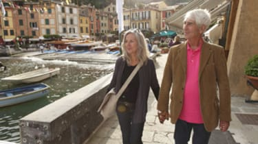 Senior couple walking by the water, Italy