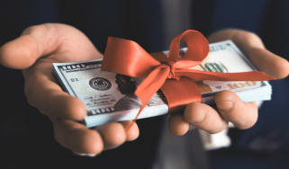 A pair of hands hold a bundle of money tied with a red ribbon.