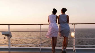 Two passengers enjoy a sunset on a cruise.