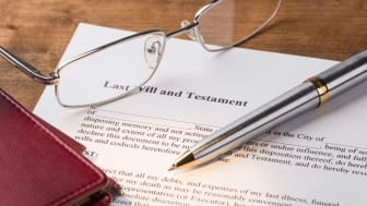 A pair of glasses and a pen sitting on a will
