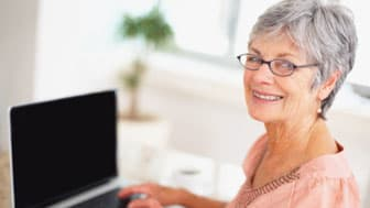 Happy elderly woman using a laptop while at home