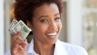 A woman holds up a $50 bill.
