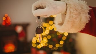 Hand of father christmas holding car key