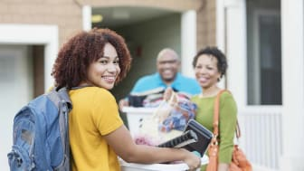Mature African-American parents helping their daughter relocate, perhaps into an apartment or college dorm.The young woman is in the foreground smiling at the camera, carrying a backpack and