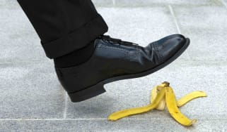 A businessperson about to step on a banana peel