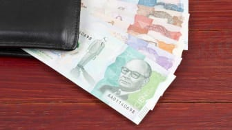 Money from Colombia in the black wallet on a wooden background