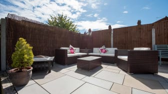 A general view of a sun terrace patio with brown rattan garden corner sofa and armchairs, fire pit and smooth stone slabs