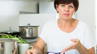 Stressful retiree woman sitting on her kitchen and looking at payment checks