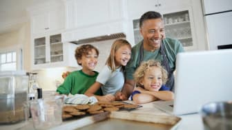 A smiling family gathered around a laptop on a kitchen counter