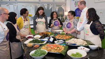 Prince William and Kate Middleton at a cooking demonstration with a group of people