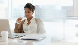A woman chews on a pen and thinks.