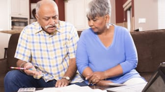 Indian man and African descent woman, senior adult couple work together to pay their monthly bills.They are calculating expenses versus budget income.Many invoices on living room table.Kitche