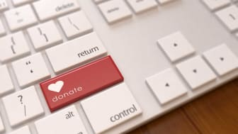 """picture of a keyboard with a red button marked with a heart and the word """"Donate"""""""