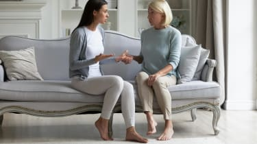 A mom and daughter talk on a couch.