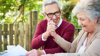 Senior couple high-five after doing their taxes