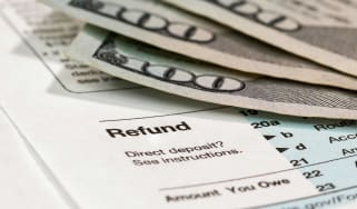 picture of a tax form showing the refund line with one-hundred dollar bills on it