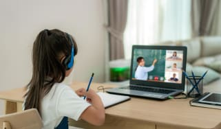 A grade school student at her home desk watches her teacher teach remotely on a laptop