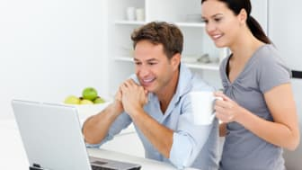 Happy couple looking at something on the laptop while drinking coffee