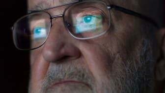 A computer screen is reflected in a senior man's eyeglasses